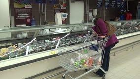 De vrouw koopt salades en andere voedingsmiddelen in supermarkten stock video