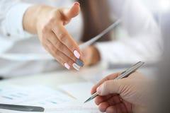 De vrouw in kostuum geeft hand zoals hello in bureauclose-up stock foto