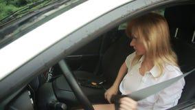 De vrouw krijgt in de auto in de regen slijtageveiligheidsgordels stock video