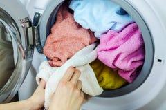 De vrouw krijgt kleren van de wasmachine Stock Foto