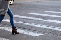 De vrouw kruist de weg bij de voetgangersoversteekplaats Het onduidelijke beeld van de motie royalty-vrije stock fotografie
