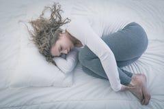 De vrouw krulde omhoog in bed royalty-vrije stock afbeelding