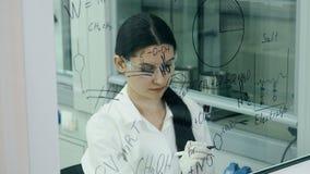 De vrouw in laboratorium schrijft formule op de glasraad stock footage