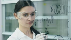 De vrouw in laboratorium schrijft formule op de glasraad stock video