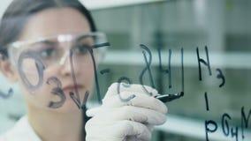 De vrouw in laboratorium schrijft formule op de glasraad stock videobeelden