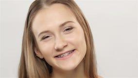 De vrouw lacht en toont haar glimlach met steunen wit Langzame Motie stock footage