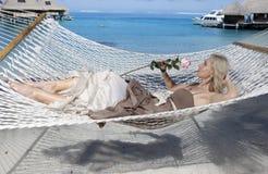 De vrouw in lange kleding met roze in hand ligt in een hangmat op achtergrond van het overzees Royalty-vrije Stock Fotografie