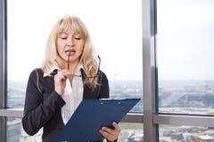 De vrouw las zorgvuldig de documenten Stock Afbeelding