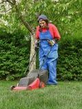 De vrouw leert hoe te om het gras te snijden Stock Foto's
