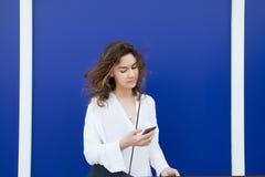 De vrouw leest berichten door celtelefoon Stock Foto's
