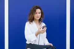 De vrouw leest berichten door celtelefoon Stock Afbeeldingen