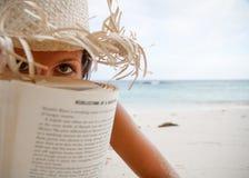 De vrouw leest een boek op strand Stock Afbeeldingen