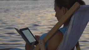 De vrouw leest een eBook bij zonsondergang dichtbij het schitteren water