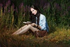 De vrouw leest het boek op de aard Royalty-vrije Stock Foto