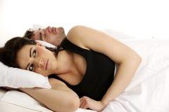 De vrouw legde in wit bed naast een slaapman Stock Foto's