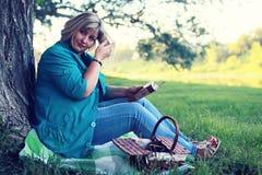 De vrouw legt en las boekzon Royalty-vrije Stock Afbeelding