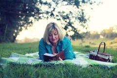De vrouw legt en las boekzon Stock Afbeelding