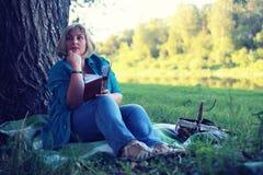 De vrouw legt en las boekzon Stock Foto