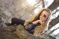 De vrouw legt op een boomboomstam Royalty-vrije Stock Foto