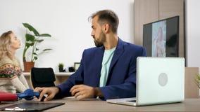 De vrouw let op TV en maakt lawaai op de achtergrond terwijl haar echtgenoot om aan laptop probeert te werken stock footage