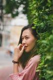 De vrouw leunt tegen een bladmuur royalty-vrije stock afbeelding