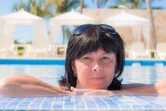 De vrouw ligt dichtbij de pool stock afbeelding