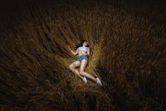 De vrouw ligt in gouden gebied van tarwe Royalty-vrije Stock Foto's