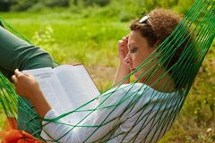 De vrouw ligt in hangmat en leest boek Royalty-vrije Stock Afbeeldingen