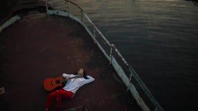 De vrouw ligt met gitaar op een oud schip stock footage