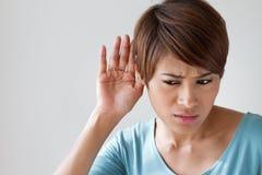 De vrouw lijdt aan beschadiging van het gehoor, hard van hoorzitting Stock Afbeelding