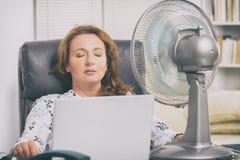 De vrouw lijdt aan hitte in het bureau of thuis royalty-vrije stock afbeelding
