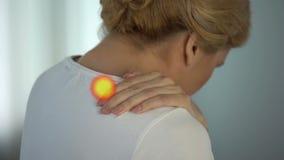 De vrouw lijdt aan schouderpijn, osteoartritis, wijst de vlek spier op pijn stock videobeelden