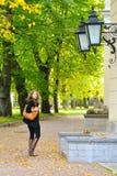 De vrouw loopt bij de herfststad Stock Afbeelding