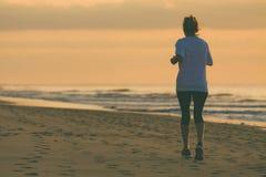 De vrouw loopt door het strand Stock Fotografie