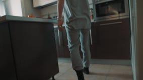De vrouw loopt door woonkamer aan keuken, zet ketel aan en leunt op lijst stock video