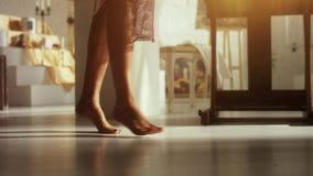 De vrouw loopt naakte voeten op aan het licht gebrachte vloer in heldere geleverde ruimte in daglicht stock videobeelden