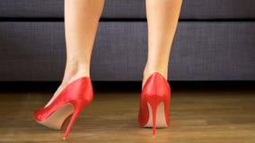 De vrouw loopt sensually in rode hoge hielen die sexy en slanke lange benen tonen stock videobeelden