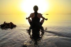 De vrouw in lotusbloem stelt bij zonsopgang Stock Foto's