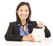 De vrouw luistert aan een spaarvarken met een stethoscoop Royalty-vrije Stock Fotografie