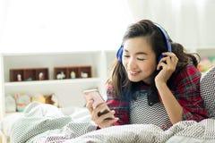 De vrouw luistert aan muziek en het gebruiken van smartphone bij haar slaapkamer stock afbeeldingen
