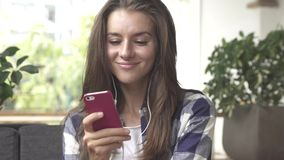 De vrouw luistert aan muziek op smartphone met oortelefoons stock footage