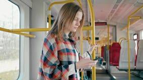 De vrouw luistert aan muziek van smartphone met oortelefoons, die door trein reizen stock video
