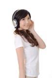 De vrouw luistert muziek stock fotografie