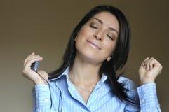 De vrouw luistert muziek Stock Foto's
