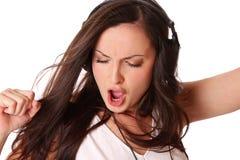 De vrouw luistert muziek op hoofdtelefoons Stock Fotografie