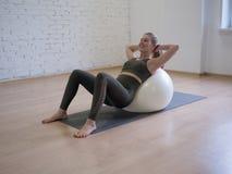 De vrouw maakt abs het gebruiken van grote geschiktheidsbal in pilatesstudio, zolderachtergrond uitoefenen royalty-vrije stock afbeeldingen