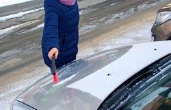 De vrouw maakt de auto van sneeuw schoon stock fotografie