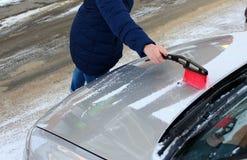 De vrouw maakt de auto van sneeuw schoon royalty-vrije stock afbeeldingen