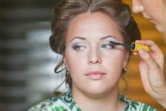 De vrouw maakt bruids make-up voor wimpers en oog door borstel voor mascara stock foto