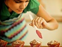 De vrouw maakt cakes in de keuken Stock Afbeelding
